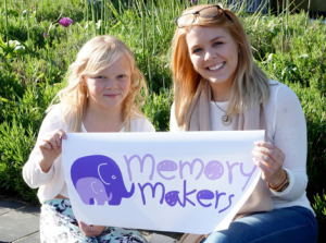 Memory Maker and child holding Memory Makers banner
